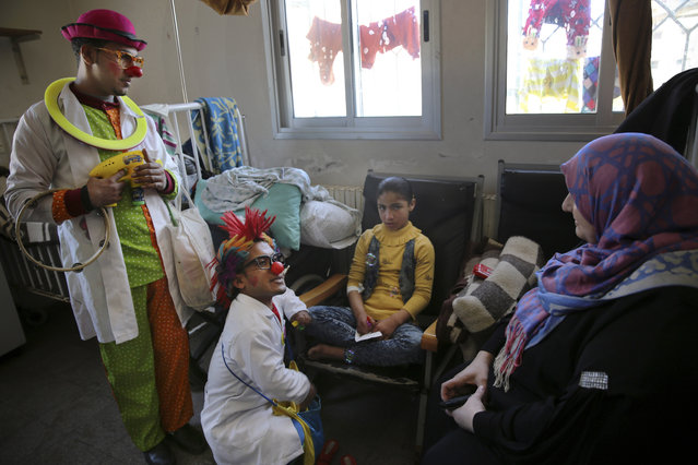 In this Thursday, March 17, 2016 photo, 33-year-old Palestinian clown doctor Alaa Miqdad, bottom center, and 24-year-old Majed Kaloub, left, entertain Shahed Mohammed, who suffers from gland disorders, in the department of kidney diseases at Al-Rantisi children's hospital in Gaza City. After and even during the war, Majed and Alaa worked on relieving children who suffered trauma due to the airstrikes. They performed in damaged neighborhoods and temporary shelters. (Photo by Adel Hana/AP Photo)