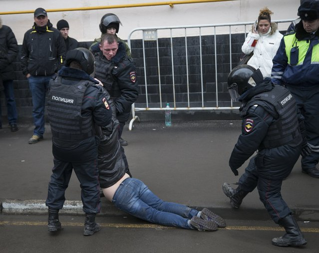 Russian police officers detain a woman, an opposition activist outside a court room in Moscow, Russia, Monday, Feb. 24, 2014. A court on Monday handed down prison sentences of up to four years for seven people who took part in a 2012 protest against Vladimir Putin. An eighth defendant received a suspended sentence. Hundreds of their supporters gathered outside the courthouse to condemn the trial and the Kremlin's crackdown on opposition. Police detained about 600 of them, accusing them of violating public order. (Photo by Alexander Zemlianichenko/AP Photo)