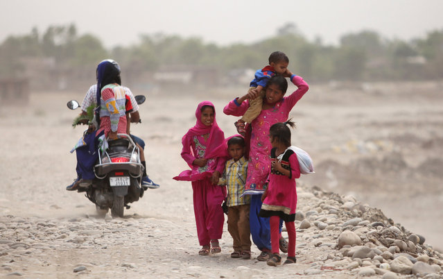 An Indian woman walks with children during a dust storm in Jammu, India, Saturday, May 9, 2015. (Photo by Channi Anand/AP Photo)