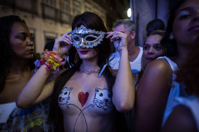 Topless dancers wait for a moment during a street parade of Banda da Rua do Mercado in Rio de Janeiro, Brazil, on Februrary 27, 2014. Rio's carnival will start officially from tomorrow for 5 days and have around 470 groups on streets. Samba school parades will have a peak at Sambodromo on March 2 and 3, 2014. (Photo by Yasuyoshi Chiba/AFP Photo)