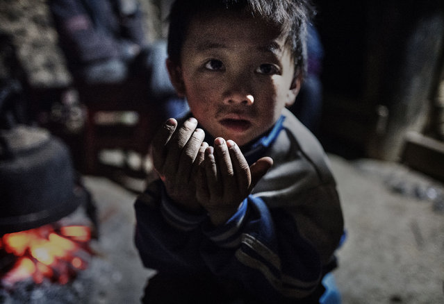 """""""Left behind"""" child Luo Lie, 5, keeps warm by a fire in the family home on December 17, 2016 in Anshun, China. (Photo by Kevin Frayer/Getty Images)"""