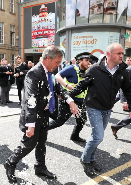 Brexit Party leader Nigel Farage gestures after being hit with a milkshake while arriving for a Brexit Party campaign event in Newcastle, Britain, May 20, 2019. (Photo by Scott Heppell/Reuters)
