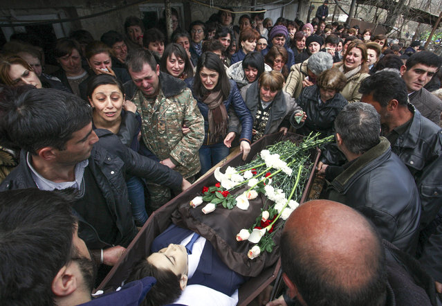 People react during a funeral for 12-year-old Vagharshak Grigoryan in a village of Martuni region of the separatist Nagorno-Karabakh region, Azerbaijan, on Monday, April 4, 2016. Grigoryan was one the first victims of the clashes that erupted between Armenian and Azerbaijani forces on April 2, 2016 as part of a territorial conflict between Armenia and Azerbaijan. Azerbaijan's defense ministry says three of its troops have been killed in the past 24 hours in fighting with the separatist region of Nagorno-Karabakh. (Photo by Vahram Baghdasaryan/Photolure Photo via AP Photo)