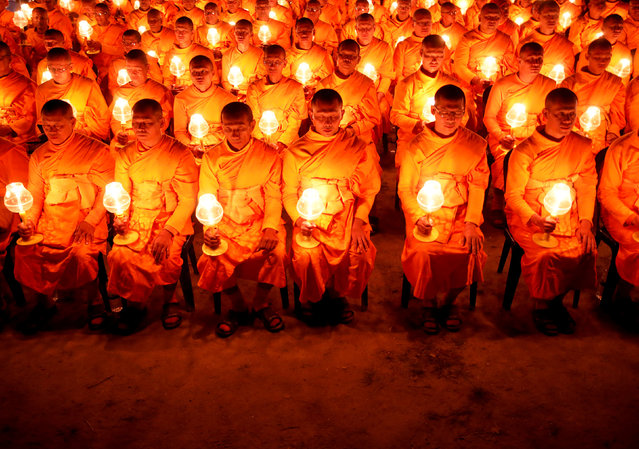 "Monks with lit candles attend an event to spread the message of ""world peace through inner peace"" in Kathmandu, Nepal March 16, 2019. (Photo by Navesh Chitrakar/Reuters)"