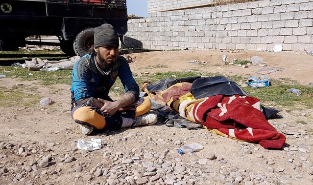 A displaced Iraqi man sits next to the body of a relative who was killed during a battle between Islamic State fighters and Iraqi troops in western Mosul, Iraq February 26, 2017. (Photo by Mahdi Talaat/Reuters)