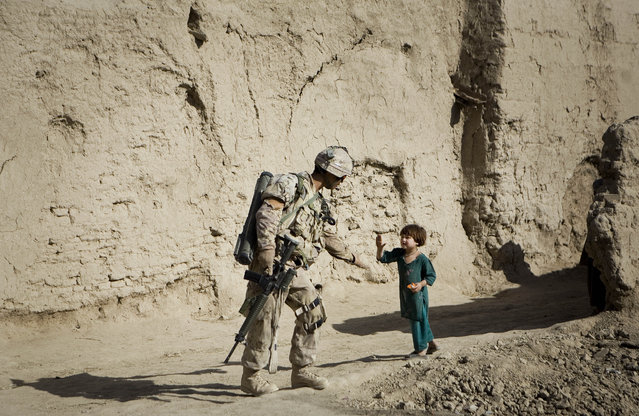 An Afghan girl greets a Canadian soldier with the 1st Battalion, The Royal Canadian Regiment, patroling Salavat, Panjwayi district, southwest of Kandahar, Afghanistan, Monday, May 31, 2010. (Photo by Anja Niedringhaus/AP Photo)