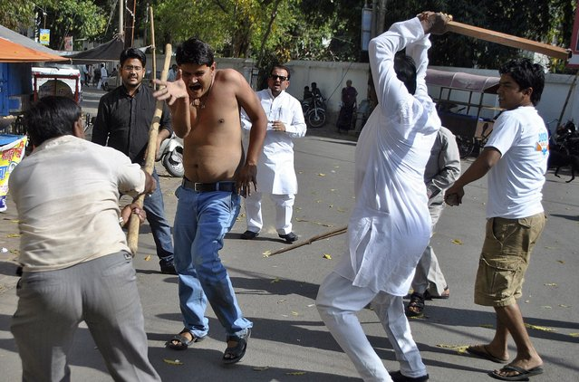 Employees of the Bundelkhand Vikas Sena (BVS) use batons to hit a worker of India's ruling Congress party during a clash at a demonstration outside the Congress office in the northern Indian city of Lucknow March 28, 2014. The BVS workers were protesting against the Congress manifesto, saying it did not have any package for the development of Bundelkhand, local media reported on Friday. (Photo by Reuters/Stringer)