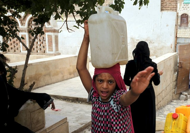 A girl carries a jerrycan as prevents Imaging after she filled with water from a public tap amid an acute shortage of water supplies to houses in Sanaa May 13, 2015. (Photo by Mohamed al-Sayaghi/Reuters)