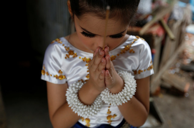A dancer prays before she performs as land activists gather to commemorate the upcoming Women's Day in Phnom Penh, Cambodia, March 7, 2017. (Photo by Samrang Pring/Reuters)