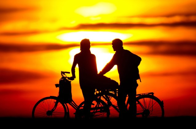 Two cyclists watch the sunset at the Teufelsberg in Berlin, Germany, 20 March 2014. (Photo by Daniel Bockwoldt/EPA)