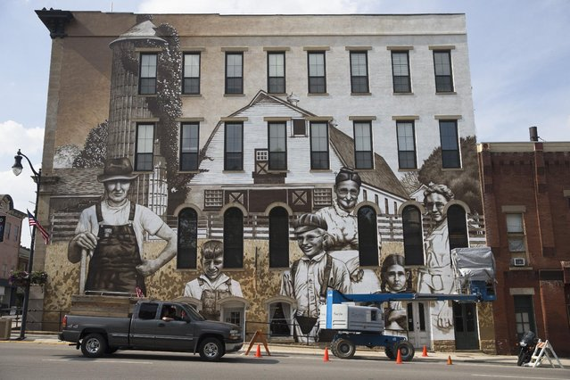 "Artist Jason Morgan works on a mural named ""Heritage Harvesters"" as commissioned by a building owner to depict farmers from the community, Thursday, June 11, 2015, in Wilmington, Ohio. Locals were asked to send photographs of their ancestors who lived in the Wilmington area to adorn the edifice that sits along the town's main drag. (AP Photo/John Minchillo)"
