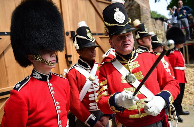 Troops stand in front of the new North Gate during the ceremonial opening of Hougoumont Farm in Braine-l'Alleud, near Waterloo, Belgium on Wednesday, June 17, 2015. Hougoumont Farm played a critical role in the outcome of the Battle of Waterloo, and the newly restored farm will open to the general public on June 18, 2015. (AP Photo/Emmanuel Dunand/Pool Photo via AP)