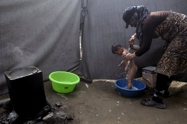 A woman washes her child at a makeshift camp for migrants and refugees at the Greek-Macedonian border near the village of Idomeni, Greece, April 24, 2016. (Photo by Alexandros Avramidis/Reuters)