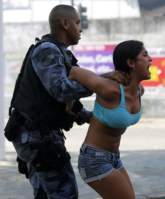 A riot policeman arrests a demonstrator in Rio de Janeiro, Brazil, on April 11, 2014. (Photo by Sergio Moraes/Reuters)