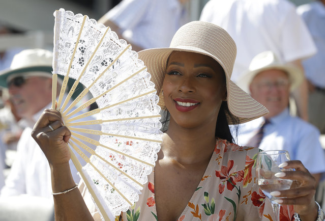 A spectator uses a fan to keep cool ahead of the second day of the test match between England and Ireland at Lord's cricket ground in London, Thursday, July 25, 2019. Weather forecasters predict the UK could encounter the hottest July day on record later Thursday. (Photo by Kirsty Wigglesworth/AP Photo)