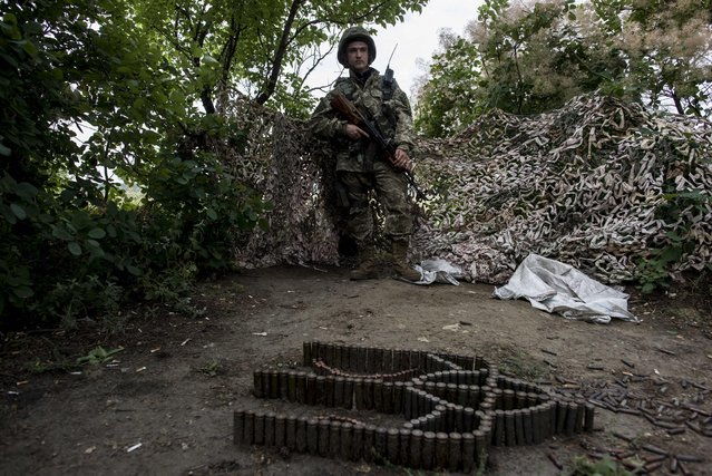 In this photo taken Tuesday, June 23, 2015, a Ukrainian serviceman from the Kiev-2 volunteer battalion guards his position at the frontline in the village of Krymske, east Ukraine. (Photo by Evgeniy Maloletka/AP Photo)