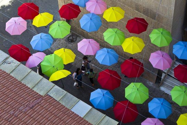 People walk under colourful umbrellas decorating a pedestrian mall in downtown Jerusalem June 30, 2015. (Photo by Ronen Zvulun/Reuters)