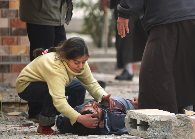 An Iraqi girl cries over her father's body, who was killed by a mortar shell fired by Islamic State (IS) group jihadists on civilians who were gathered to receive aid, in Al-Risala neighbourhood on March 22, 2017, as an ongoing offensive by Iraqi forces to retake the city from the group continues. Iraqi forces launched a major operation to recapture west Mosul – the most-populated urban area still held by IS – on February 19, and have retaken a series of neighbourhoods from the jihadists. (Photo by Ahmad Al-Rubaye/AFP Photo)