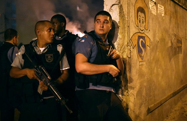 Rio de Janeiro's state military policemen stand in position during a violent protest in a favela next to Copacabana, Rio de Janeiro on April 22, 2014. Violent protests broke out in Rio's landmark beachfront district, Copacabana, following the death of a resident last weekend during clashes with the Army in a nearby favela. (Photo by Christophe Simon/AFP Photo)