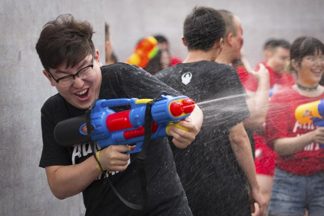 A player fires his water gun in a battle maze in Beijing, Saturday, July 4, 2015. (Photo by Mark Schiefelbein/AP Photo)