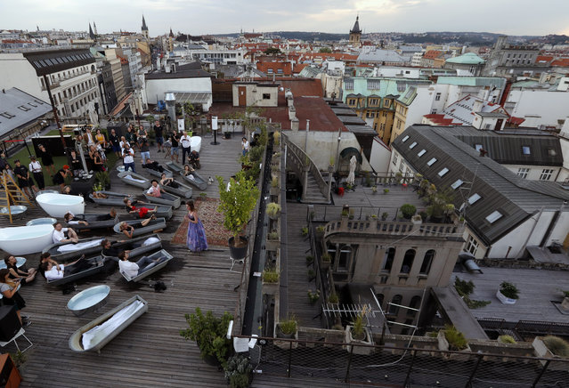 Spectators soak in bathtubs while listening to Czech opera singer Eva Kyvalova performing parts of Mozart's Don Giovanni at the rooftop of Lucerna building in Prague, Czech Republic, Thursday, August 29, 2019. (Photo by Petr David Josek/AP Photo)