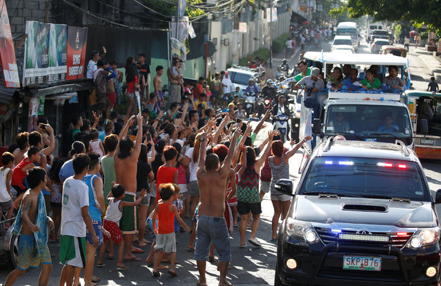 Supporters wave at the motorcade of Presidential candidate Jejomar Binay and Filipino boxer and Senatorial candidate Manny Pacquiao during election campaigning in Malabon Metro Manila in the Philippines May 6, 2016. (Photo by Erik De Castro/Reuters)