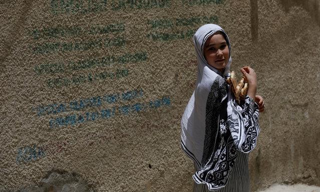 A Hazara girl walks holding naans (breads) along a street in Hazara Town, Quetta, Pakistan, June 13, 2019. (Photo by Akhtar Soomro/Reuters)