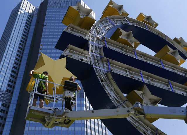 Workers dismantle the large Euro sign sculpture for maintenance, in front of the headquarters of the former European Central Bank (ECB) in Frankfurt, July 6, 2015.  The large blue and yellow sculpture was made by German artist Ottmar Hoerl in 2001. (Photo by Ralph Orlowski/Reuters)