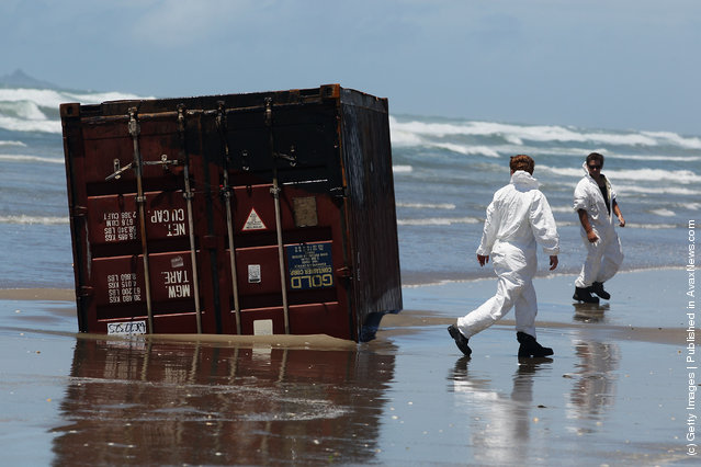 Residents check washed up containers at Waihi Beach in Tauranga, New Zealand