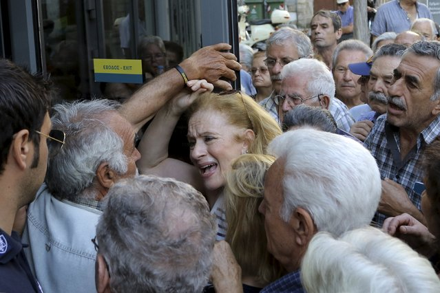 A pensioner (C) reacts as she tries to enter a National Bank branch to receive part of her pension at the city of Iraklio in the island of Crete, Greece July 9, 2015. A race to save Greece from bankruptcy and keep it in the euro gathered pace on Wednesday when Athens formally applied for a three-year loan and European authorities launched an accelerated review of the request. (Photo by Stefanos Rapanis/Reuters)