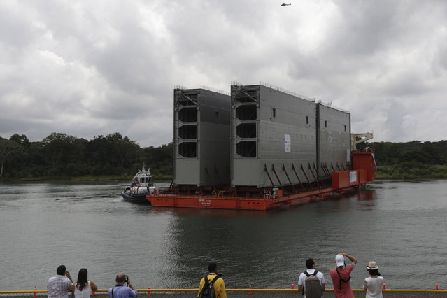Members of the media film the first four new gates for the Panama Canal's third set of locks which are on top of a cargo ship during the arrival to Colon in Colon City August 22, 2013. (Photo by Carlos Jasso/Reuters)