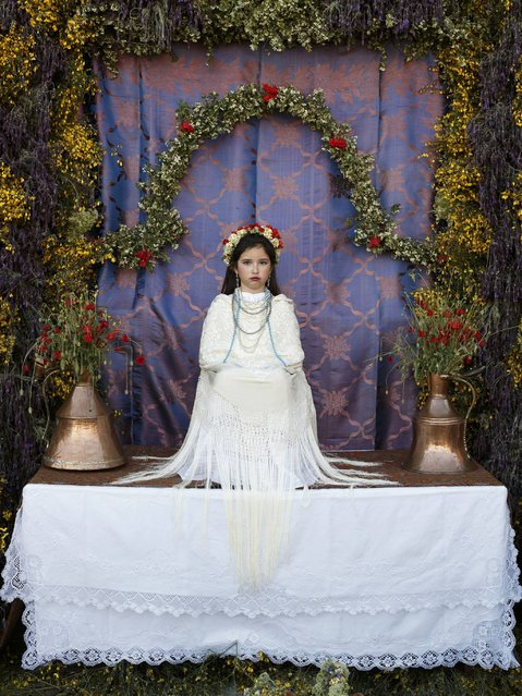 "A ""Maya"" girl sits in an altar during the traditional celebration of ""Las Mayas"" on the streets in Colmenar Viejo, near Madrid, Spain, Friday, May 2, 2014. (Photo by Daniel Ochoa de Olza/AP Photo)"