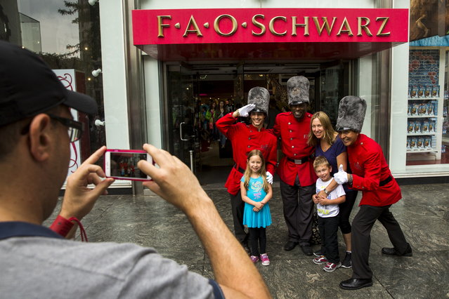 Tourists pose with costumed employees outside of the toy store July 15, 2015. The store, which has been the face of FAO Schwarz since 1986, is moving from its location on fashionable Fifth Avenue due to rising rent. It will continue to look for an alternative location in midtown Manhattan, according to a statement released by the store in May. (Photo by Lucas Jackson/Reuters)