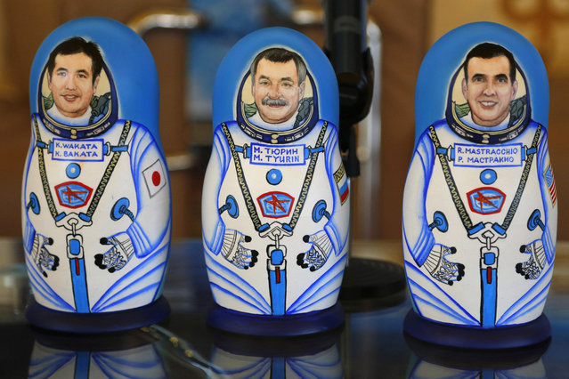 Traditional Russian Matryoshka wooden dolls depicting (L-R) Japanese astronaut Koichi Wakata, Russian cosmonaut Mikhail Tyurin and U.S. astronaut Rick Mastracchio, stand on a table during a welcoming ceremony at the airport in Karaganda, Kazakhstan, May 14, 2014. (Photo by Dmitry Lovetsky/Reuters)