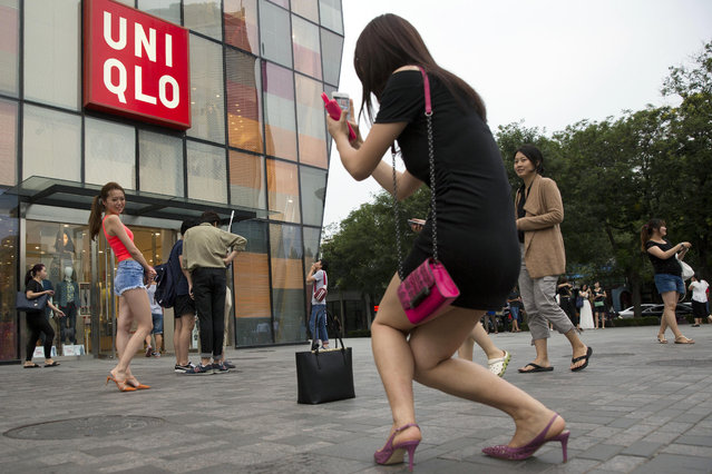 A Chinese woman poses for photo outside the Uniqlo flagship store where a steamy video purportedly taken inside one of its fitting room showing a couple apparently having s*x in Beijing, Thursday, July 16, 2015. While online searches for the Japanese clothing brand soared after the viral spread of the video, it has also drawn the concern of the police and China's highest web regulator who are investigating whether it was a vulgar marketing gimmick. (Photo by Ng Han Guan/AP Photo)