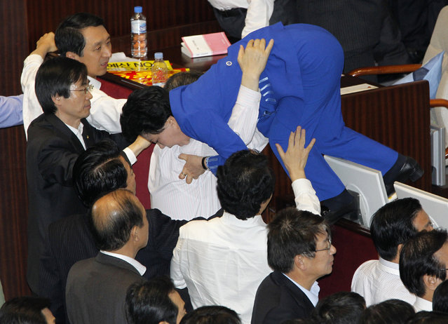 Lawmakers of opposition parties help their fellow lawmaker (top) who tries to escape as they scuffle with lawmakers of the ruling Grand National Party (GNP) at the National Assembly plenary session hall in Seoul, December 8, 2010. (Photo by Jo Yong-Hak/Reuters)