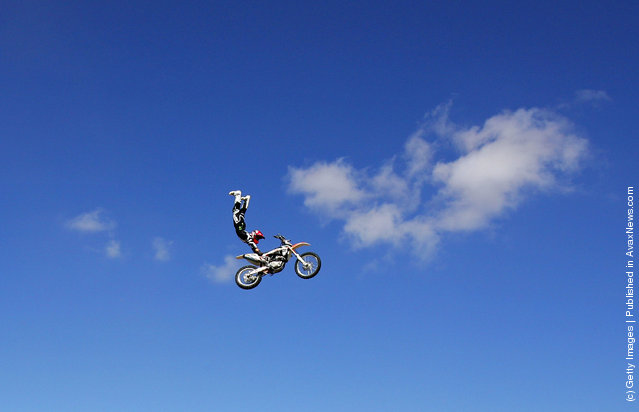 Australian Motorcross rider and member of the Crusty Demons, Robbie Marshall jumps over a helicopter with rotating blades and a Formula 1 car at Avalon Airport