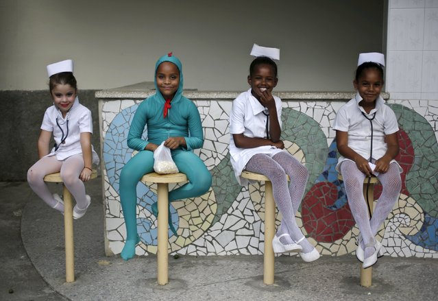 Cuban girls dressed as nurses and a lizard wait for their turn to dance during a visit by the Gay Men's Chorus of Washington in Havana July 13, 2015. The choir made its first appearance on July 12, 2015 in Cuba as part of a tour that will include a dozen concerts in the context of the restoration of relations between the island and the United States. (Photo by Enrique de la Osa/Reuters)