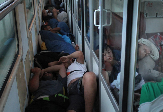 Migrants from Syria, Iraq and Afghanistan, on their way to European Union countries, sleep in a crowded the hallway of the train that runs on the north from the southern Serbian city of Presevo to Subotica, early 22 July 2015. The migrants are finding their way to wealthy countries such as Germany. Many of them enter the Balkans via EU member Greece and, after hiking across Macedonia and Serbia, intend to cross back into the European Union through Hungary. (Photo by Djordje Savic/EPA)