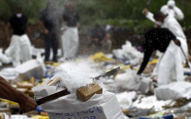 A member of the national police destroys drug packages before incinerating them in Panama City, July 23, 2015. According to Panama's anti-narcotics police, more than 5,000, kg (11,023 lbs) of cocaine and other types of drugs seized during various police operations across the country were destroyed. (Photo by Carlos Jasso/Reuters)