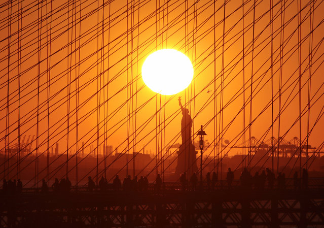 People walk on the Brooklyn Bridge as the sun sets behind the Statue of Liberty on November 4, 2019 in New York City. (Photo by Gary Hershorn/Getty Images)