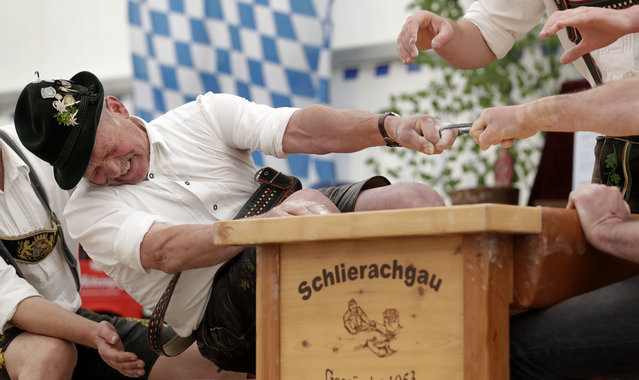 Georg Schoettl from Ohlstadt near Murnau tries to pull his opponent over the table at the 40th Alpine Country Championships in Fingerhakeln_finger wrestling_ in Woernsmuehl, Germany, Thursday, May 25, 2017. Competitors battled for the title in this traditional rural sport where the winner has to pull his opponent over a marked line on the table. (Photo by Matthias Schrader/AP Photo)