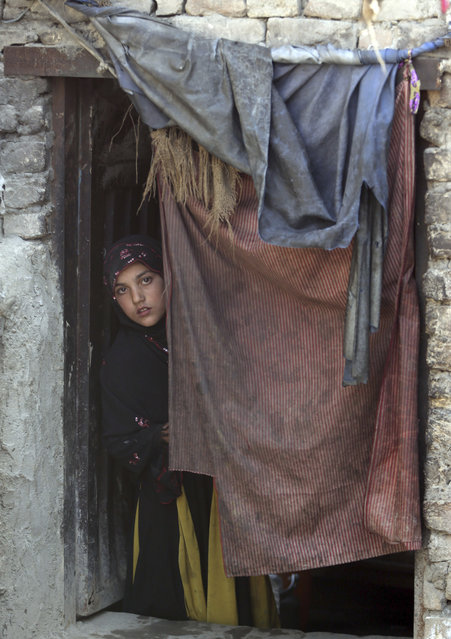 In this Sunday, March 19, 2017 photo, a young women looks on through a door in her home in Kabul, Afghanistan, Sunday, March 19, 2017. An aid group says nearly a third of all children in war-torn Afghanistan are unable to attend school, leaving them at increased risk of child labor, recruitment by armed groups, early marriage and other forms of exploitation. (Photo by Massoud Hossaini/AP Photos)
