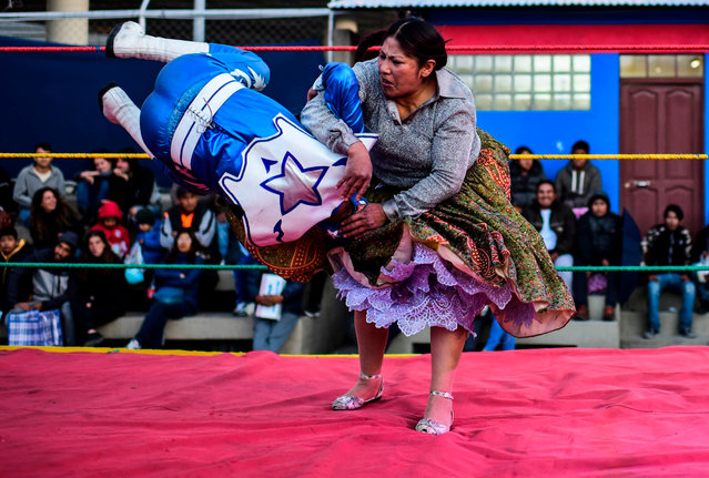 """Bolivian wrestler Ana Luisa Yujra (R), aka """"Jhenifer Two Faces"""", a member of the Fighting Cholitas, fights with a male wrestler at Sharks of the Ring wrestling club in El Alto, Bolivia, on November 24, 2019. (Photo by Ronaldo Schemidt/AFP Photo)"""