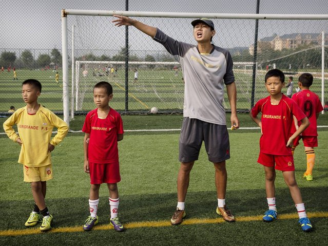A Chinese coach shouts to players as young students wait to be subbed in during a training match at the Evergrande International Football School near Qingyuan in Guangdong Province. (Photo by Kevin Frayer/Getty Images)