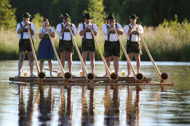 """Musicians of the alphorn band """"Holdersberger Alp- Traum- Blaeser"""" perform their skills on a raft floating on the Elbsee lake near Aitrang, southern Germany, on June 11, 2017. (Photo by Karl-Josef Hildenbrand/AFP Photo/DPA)"""