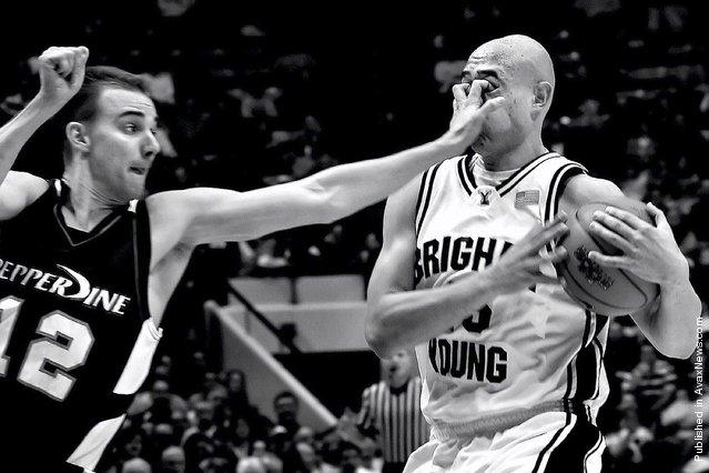 Pepperdine's Jason Walberg gouges the eyes of Brigham Young University's Jonathan Tavernari during a basketball match