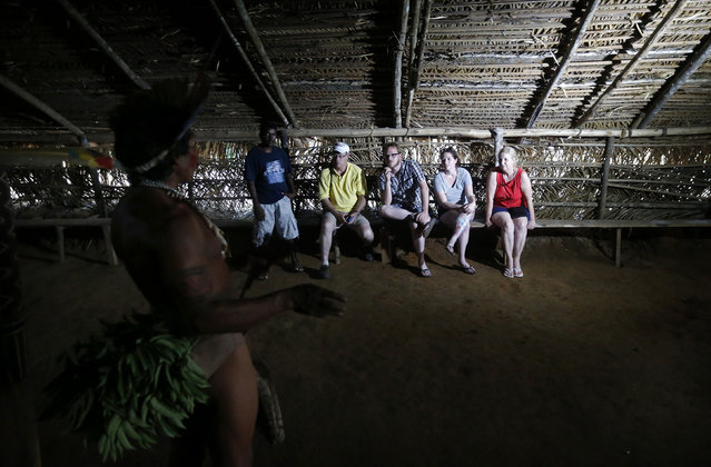 Tatuyo tribe leader Pino (L) explains to tourists some tribal rituals in their village in the Rio Negro (Black River) near Manaus city, a World Cup host city, June 23, 2014. Because of their proximity to host city Manaus and their warm welcome, the Tatuyo have enjoyed three weeks of brisk business thanks to the World Cup. Usually, they host between 10 and 30 tourists a day. During the World Cup, this number has rocketed to 250 a day, They have become richer and other communities now come to them to sell them juices and fishes. (Photo by Andres Stapff/Reuters)