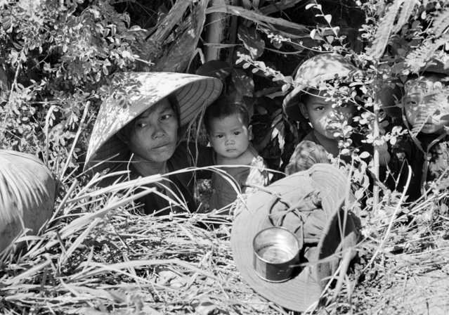 A Vietnamese woman and her children crouch in a hole at the edge of a battlefield 15 miles northeast of Toy Hoa, where a battalion of the U.S. 1st Brigade, 101st Airborne Division, reinforced by the 1st Cavalry, was defending its jungle hilltop positions against an estimated regiment of North Vietnamese regulars, June 22, 1966. Most civilians had taken cover during during several days of fighting. A U.S. soldier had given this family a C-ration in the tin can, while the hat under it once belonged to a North Vietnamese soldier. (Photo by Henri Huet/AP Photo)