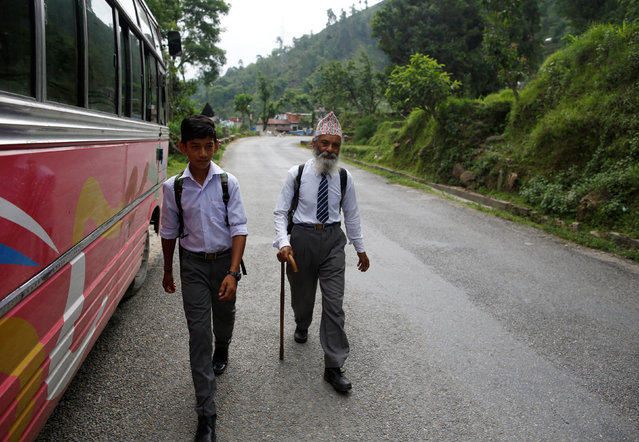 Durga Kami, 68, who is studying tenth grade at Shree Kala Bhairab Higher Secondary School, walks with his classmate Sagar Thapa, 14, as they head to school in Syangja, Nepal, June 5, 2016. (Photo by Navesh Chitrakar/Reuters)